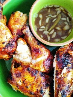 Chicken Inasal quartered alongside a coconut vinegar dip with chili peppers