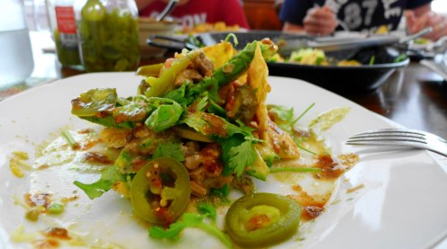 On the plate nachos with chile verde sauce and hot salsa